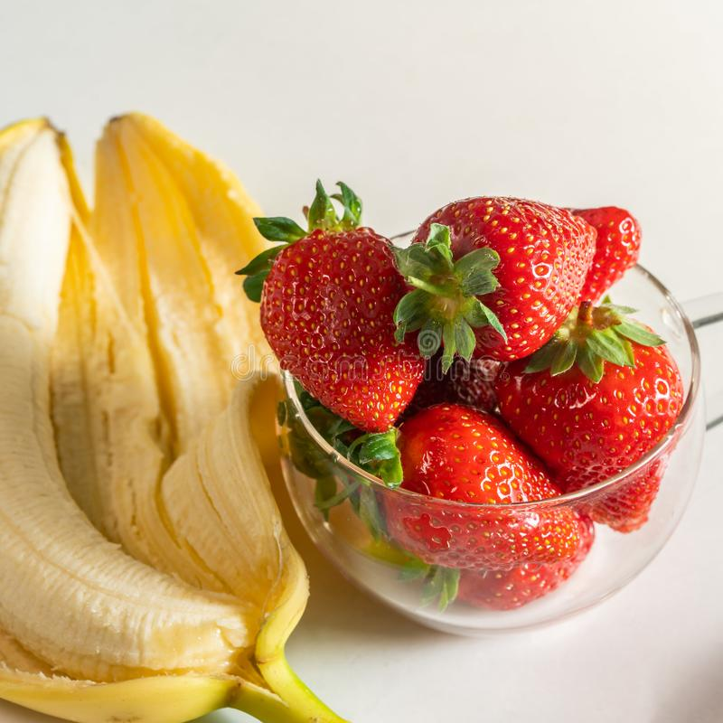 Strawberries and bananas are on the table stock photo