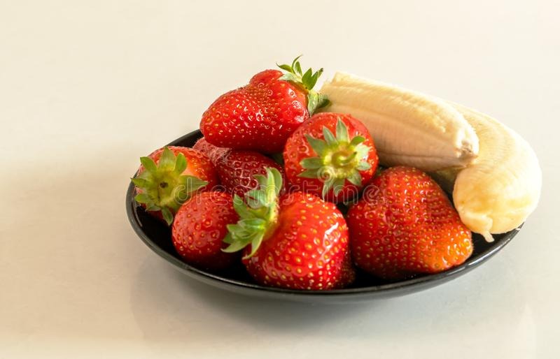 Strawberries and bananas are on the table royalty free stock image