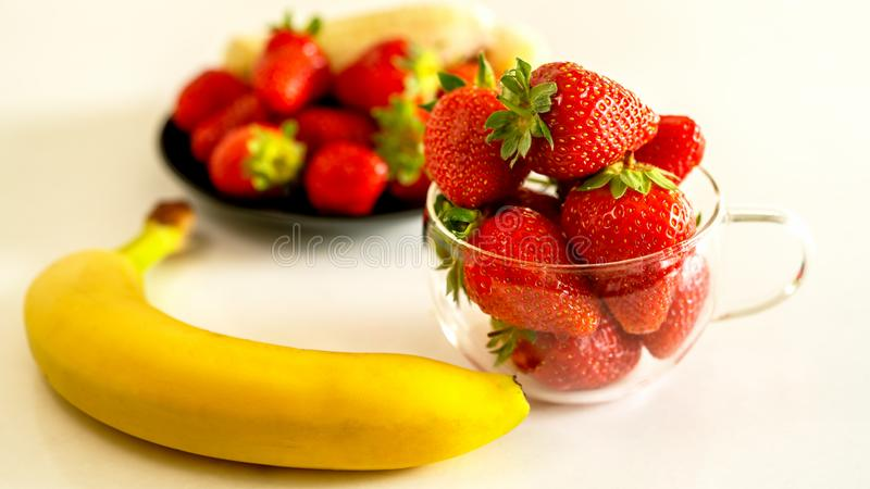 Strawberries and bananas are on the table. Fruit dessert stock images