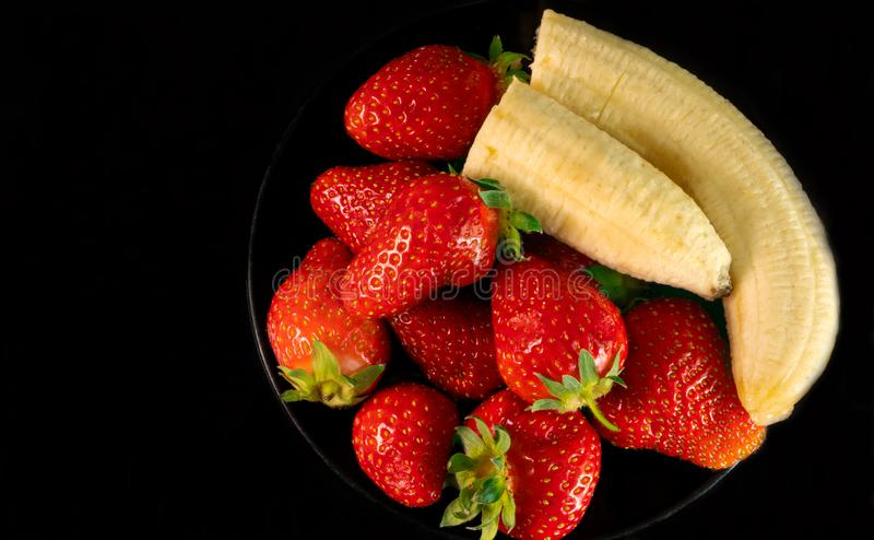 Strawberries and bananas are on the table royalty free stock photo