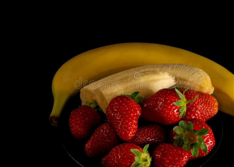Strawberries and bananas are on the table royalty free stock images