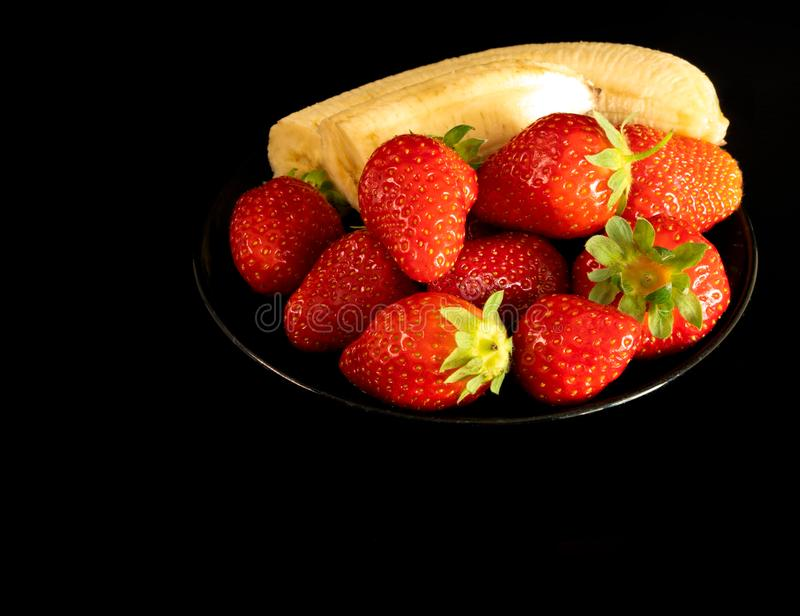 Strawberries and bananas are on the table royalty free stock photos