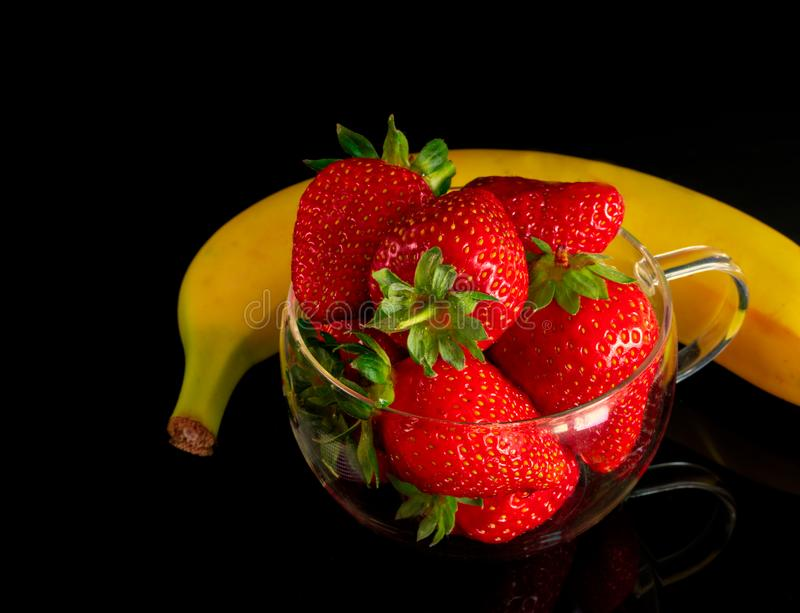 Strawberries and bananas are on the table stock image