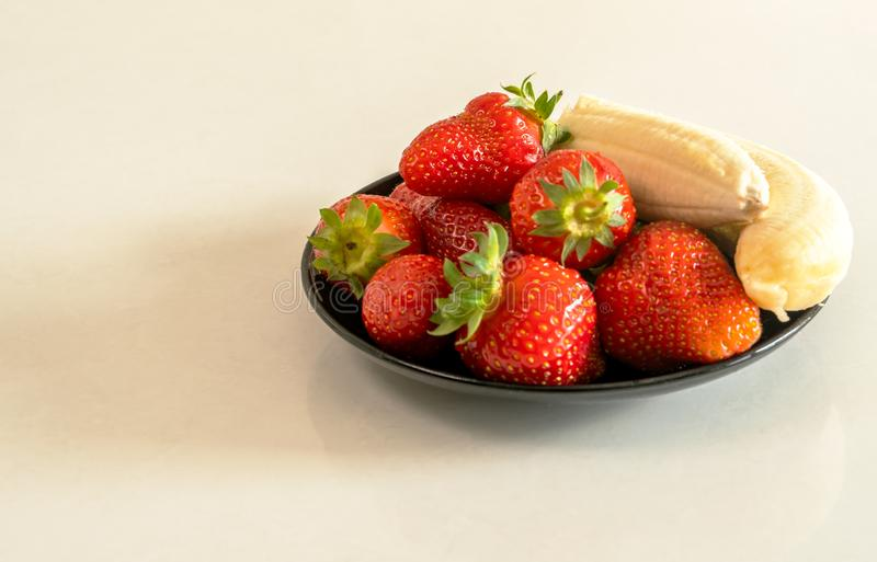 Strawberries and bananas are on the table. Fruit dessert royalty free stock photo