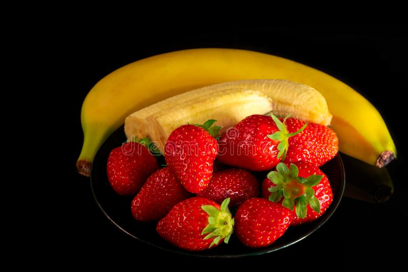 Strawberries and bananas are on the table royalty free stock photography