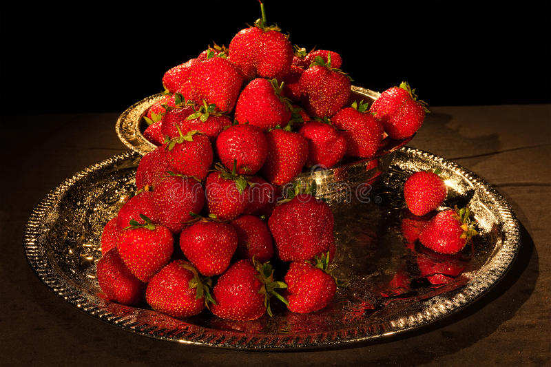 Strawberries berry on a black background with water drops stock photography