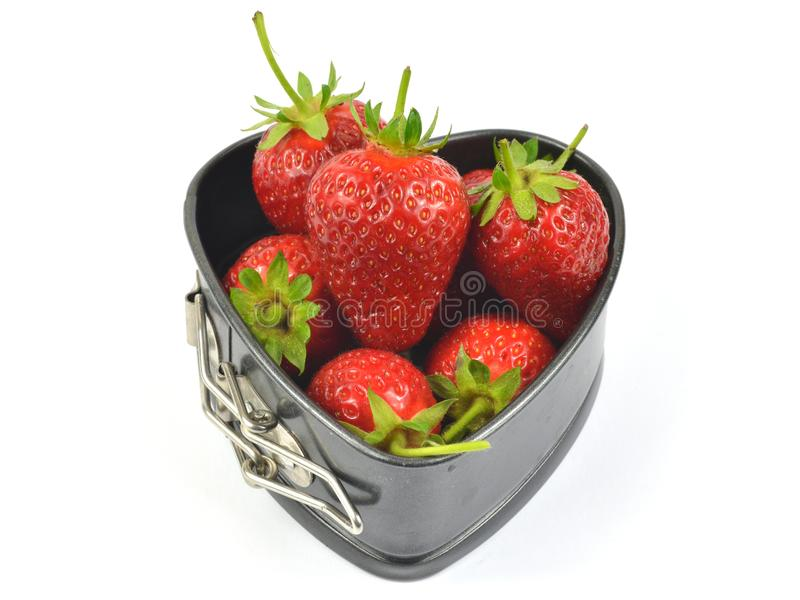 Strawberries in a black pan. Red strawberries in a backing heart shaped souffle pan on white background stock image
