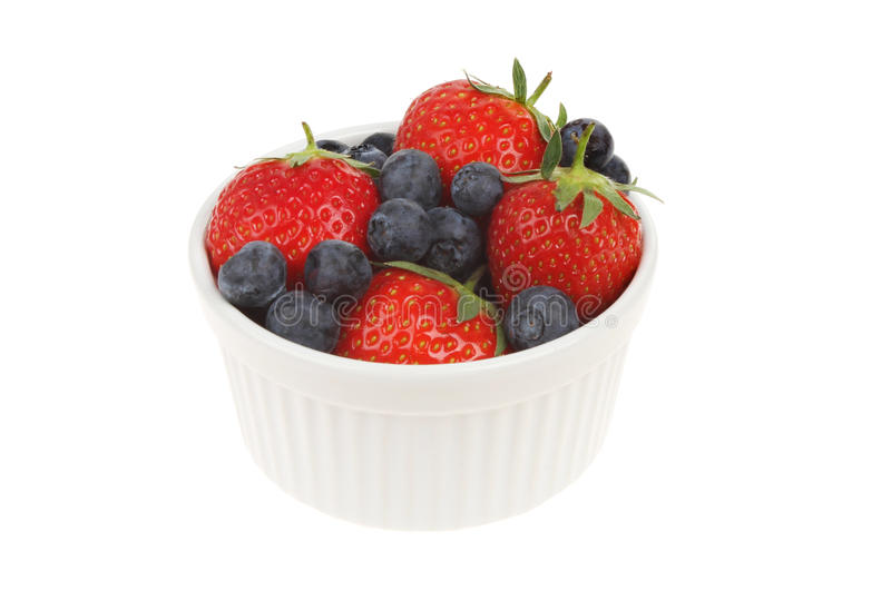 Strawberries and blueberries. In a ramekin isolated against white royalty free stock photo