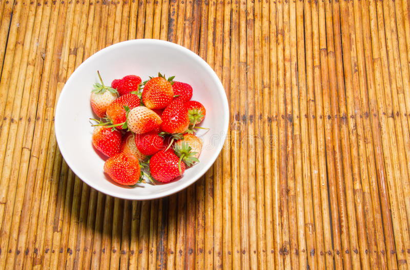 Strawberries in bowl,rattan background,select focus at strawberries stock photos