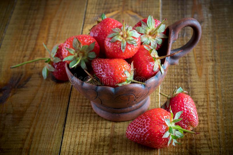 Strawberries in a clay Cup on a wooden table. stock image