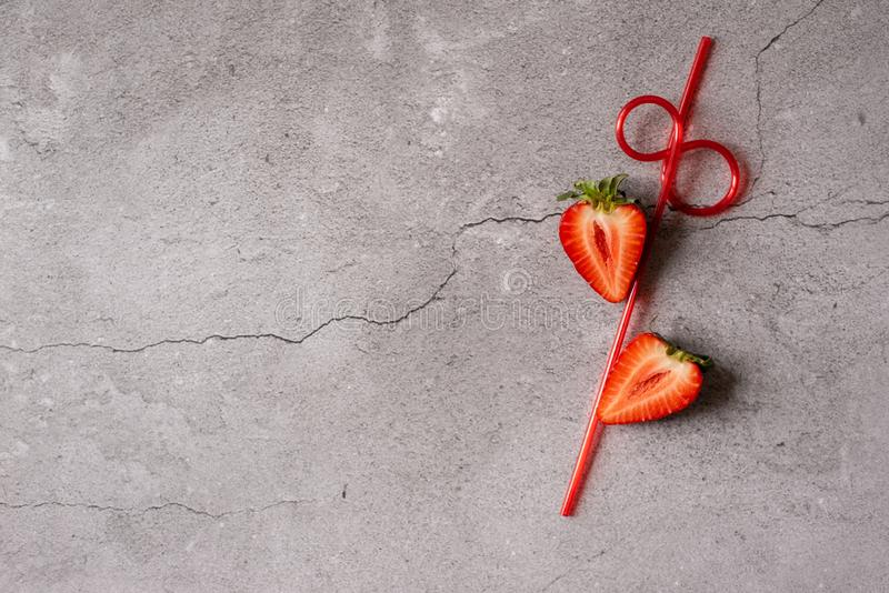 Strawberries cut with a straw on a gray background.the concept of summer stock images