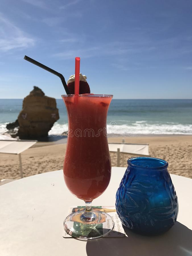 Strawberries daiquiri on the seaside. Strawberry daiquiry cocktail on the Albufeira sea coasts. Rock in the ocean. Sunny day on a beachof Portugal stock photos