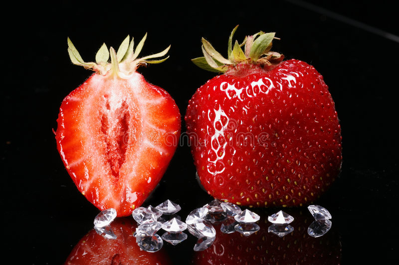 Strawberries and diamonds. Strawberries on black reflective surface with diamonds