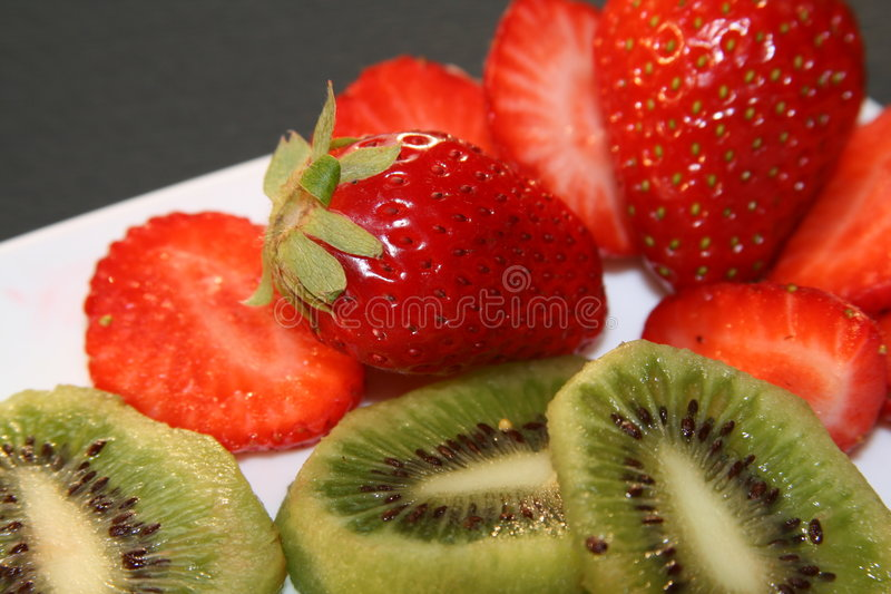 Strawberries and Kiwi. Fresh Strawberries and Kiwi slices which are ready to eat for a good dose of vitamins and healthy diet stock photos