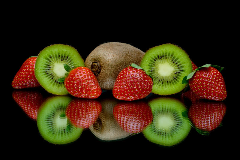 Strawberries and kiwi on a black background with reflection royalty free stock photo