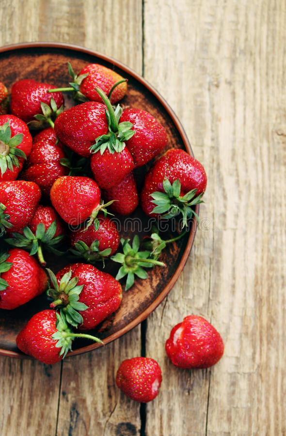 Strawberries in an old clay bowl, top view stock photos