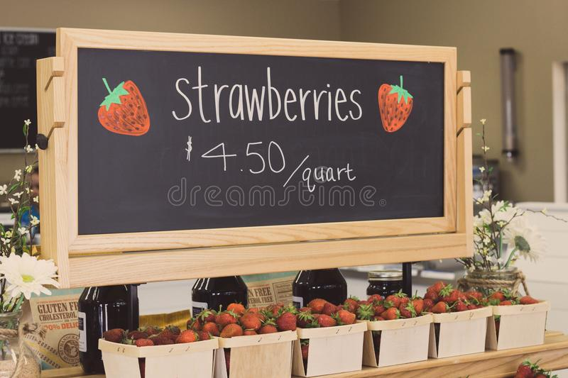 Strawberries for 4.50 Per Quartz Signage Above Bunch of Strawberries stock photography