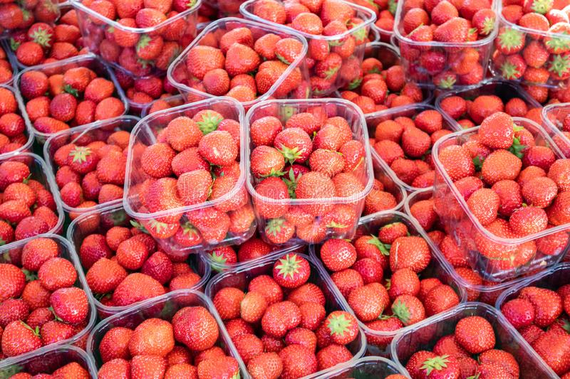 Strawberries in plastic containers at farmers market, background, texture. Close up view royalty free stock photo