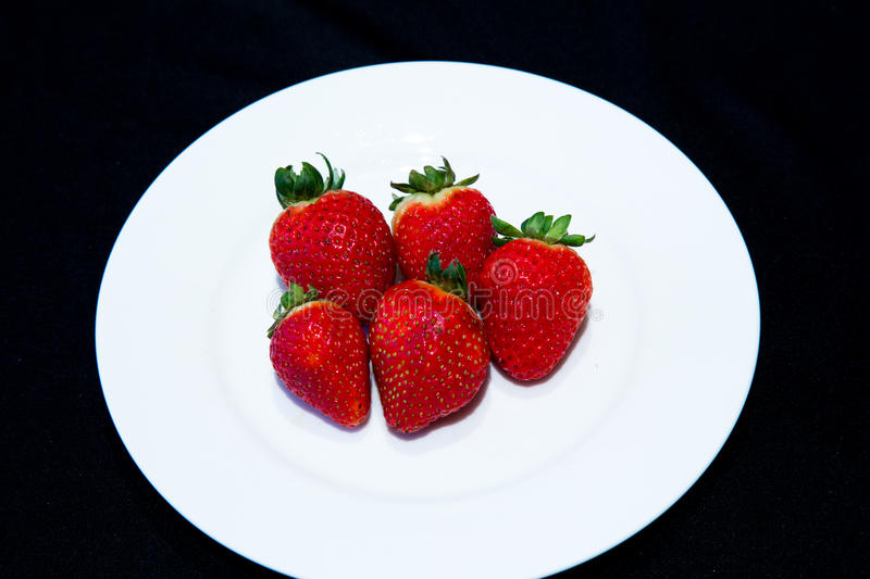 Strawberries on a plate. Red strawberries on a white plate over black background royalty free stock image