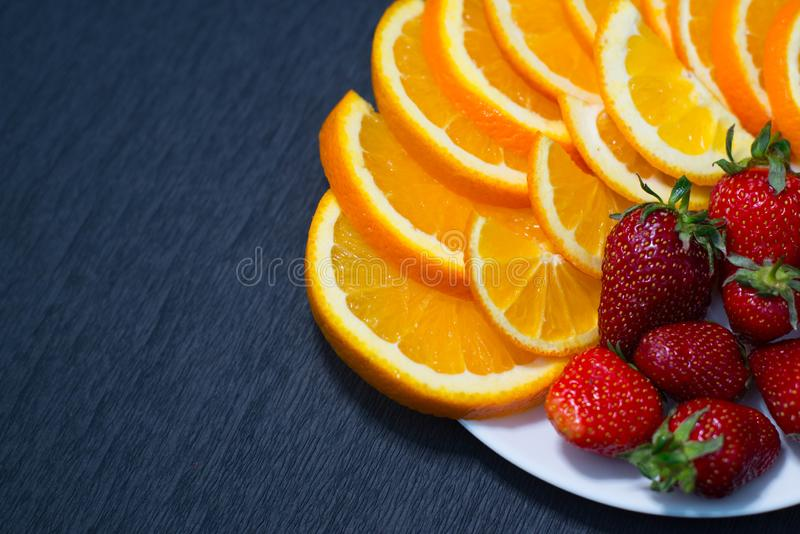 Strawberries on a plate and sliced ​​orange royalty free stock images