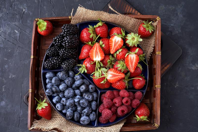 Strawberries, raspberries, blueberries, blackberries on a separate dish close-up on a solid concrete background. Healthy eating. Vegan food. View from above stock photography