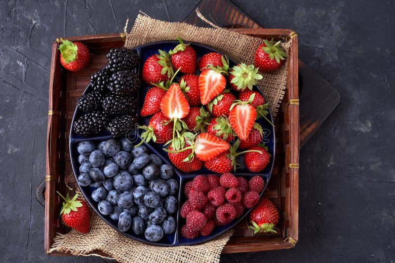 Strawberries, raspberries, blueberries, blackberries on a separate dish close-up on a solid concrete background. Healthy eating. Vegan food. View from above royalty free stock photography