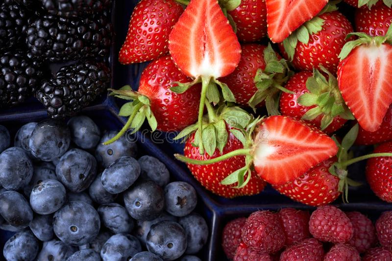 Strawberries, raspberries, blueberries, blackberries on a separate dish close-up on a solid concrete background. Healthy eating. Vegan food. View from above stock photo