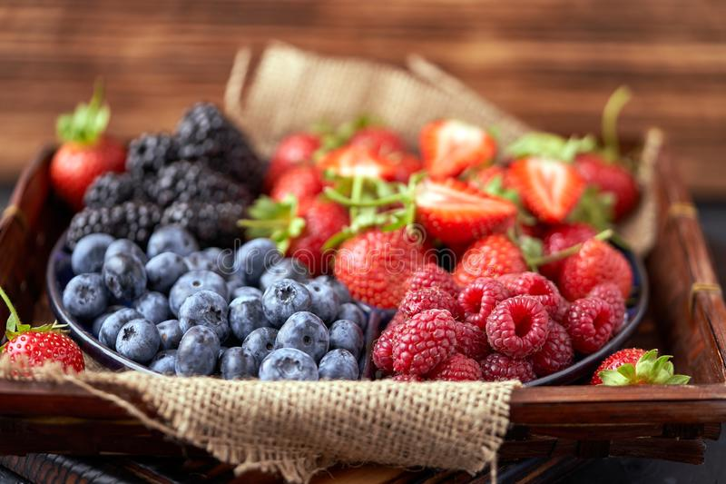 Strawberries, raspberries, blueberries, blackberries on a separate dish close-up on a solid concrete background. Healthy eating. Vegan food. Foods high in royalty free stock photo