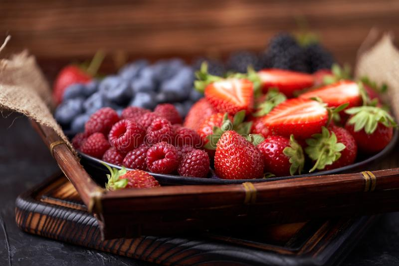 Strawberries, raspberries, blueberries, blackberries on a separate dish close-up on a solid concrete background. Healthy eating. Vegan food. Foods high in stock photography
