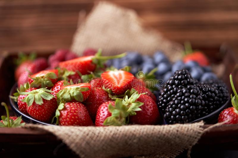 Strawberries, raspberries, blueberries, blackberries on a separate dish close-up on a solid concrete background. Healthy eating. Vegan food. Foods high in royalty free stock photography