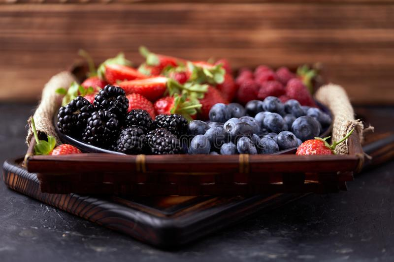 Strawberries, raspberries, blueberries, blackberries on a separate dish close-up on a solid concrete background. Healthy eating. Vegan food. Foods high in stock image