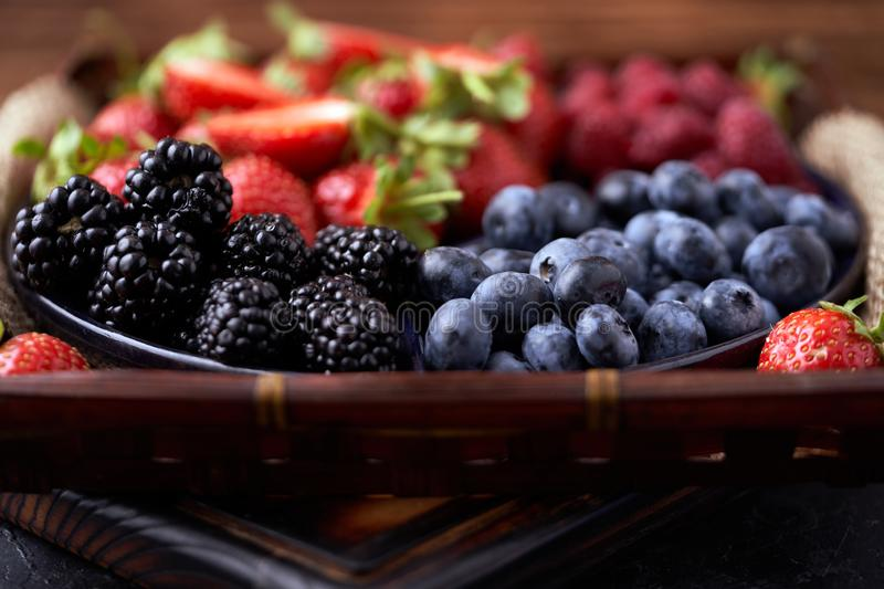 Strawberries, raspberries, blueberries, blackberries on a separate dish close-up on a solid concrete background. Healthy eating. Vegan food. Foods high in royalty free stock photos
