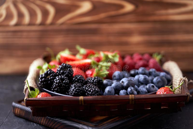 Strawberries, raspberries, blueberries, blackberries on a separate dish close-up on a solid concrete background. Healthy eating. Vegan food. Foods high in royalty free stock image