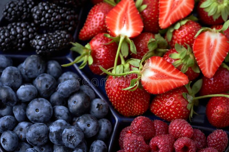 Strawberries, raspberries, blueberries, blackberries on a separate dish close-up on a solid concrete background. Healthy eating. Vegan food. View from above royalty free stock photos