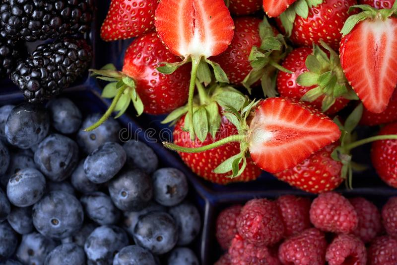 Strawberries, raspberries, blueberries, blackberries on a separate dish close-up on a solid concrete background. Healthy eating. Vegan food. View from above royalty free stock photo