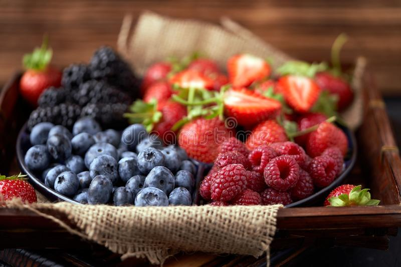 Strawberries, raspberries, blueberries, blackberries on a separate dish close-up on a solid concrete background. Healthy eating. Vegan food. Foods high in royalty free stock images