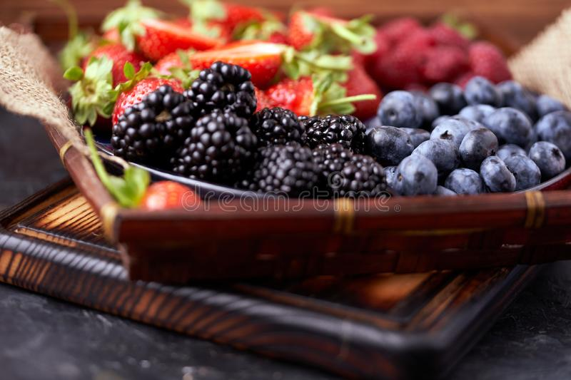 Strawberries, raspberries, blueberries, blackberries on a separate dish close-up on a solid concrete background. Healthy eating. Vegan food. Foods high in stock photos