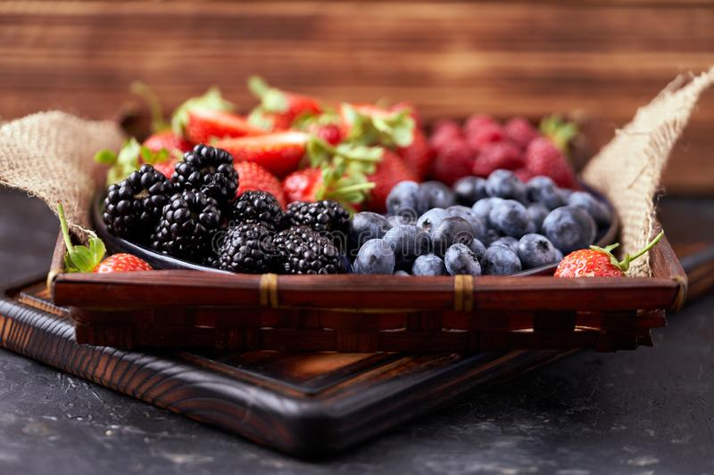 Strawberries, raspberries, blueberries, blackberries on a separate dish close-up on a solid concrete background. Healthy eating Vegan food. Foods high in royalty free stock photography
