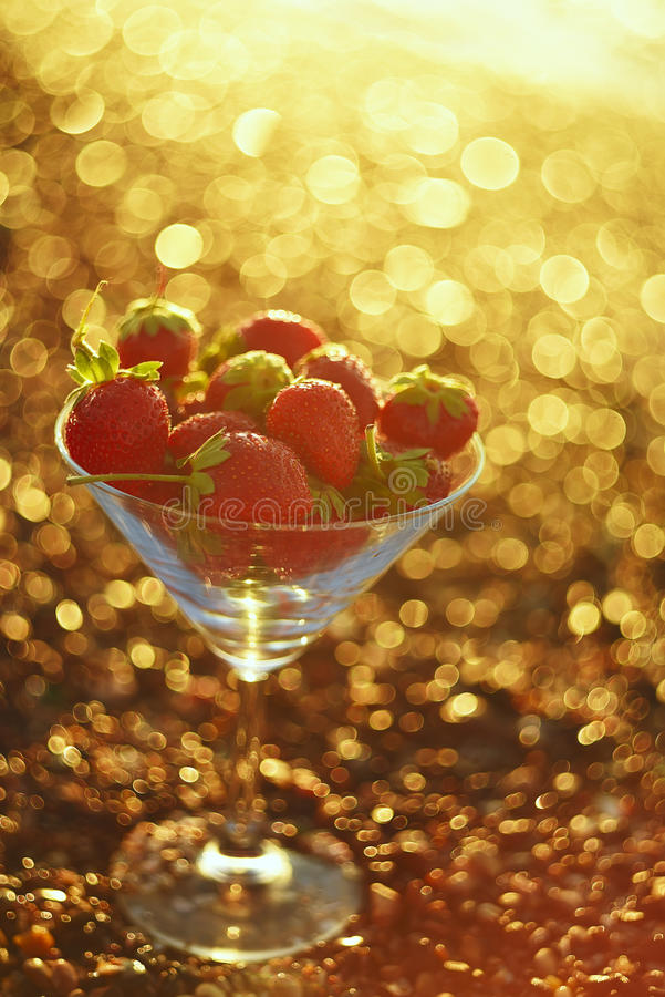 Strawberries on a sandy beach in a glass bowl. stock photography
