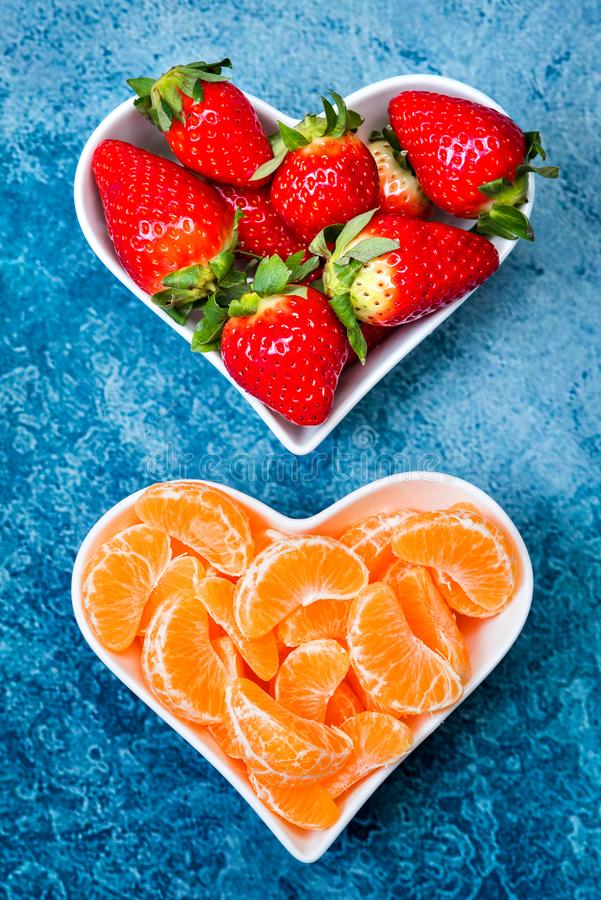 Strawberries and tangerine slices in plates royalty free stock images