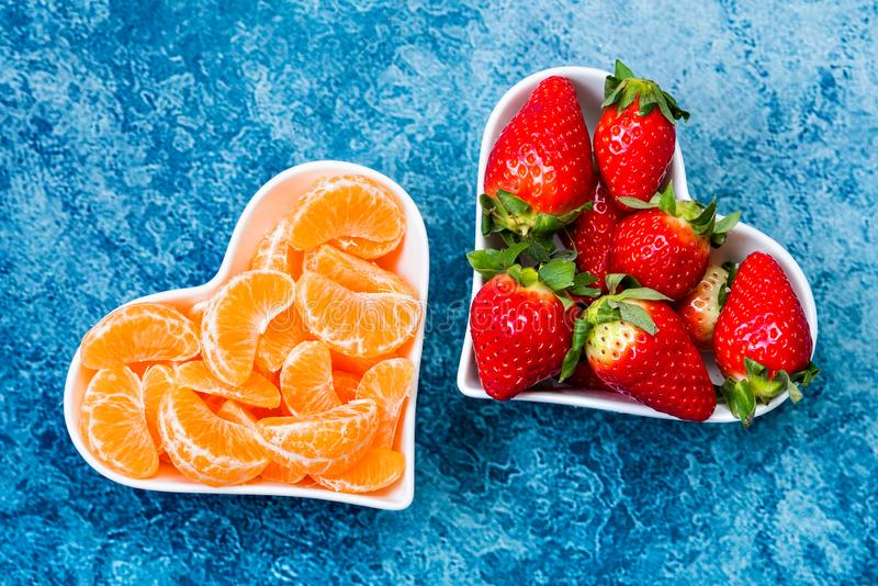 Strawberries and tangerine slices in plates royalty free stock image