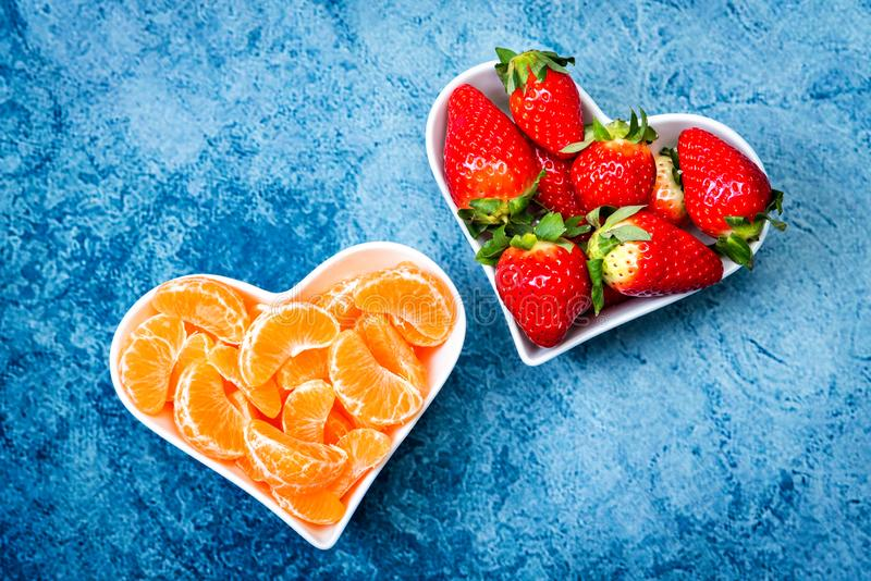 Strawberries and tangerine slices in plates stock images
