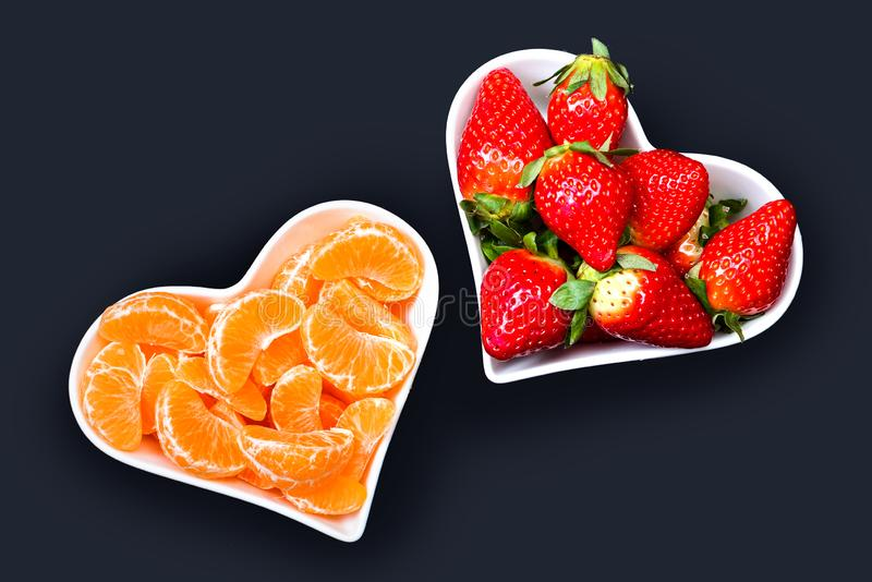 Strawberries and tangerine slices in white plates royalty free stock photography