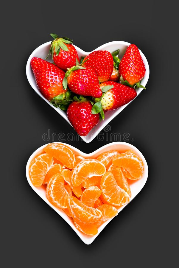 Strawberries and tangerine slices in white plates stock photography