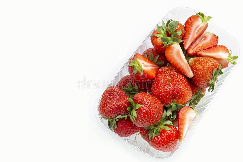 Strawberries in a transparent plastic package.Summer berry season.Isolated objects on white background. Benefit. Strawberries in a transparent plastic package royalty free stock image
