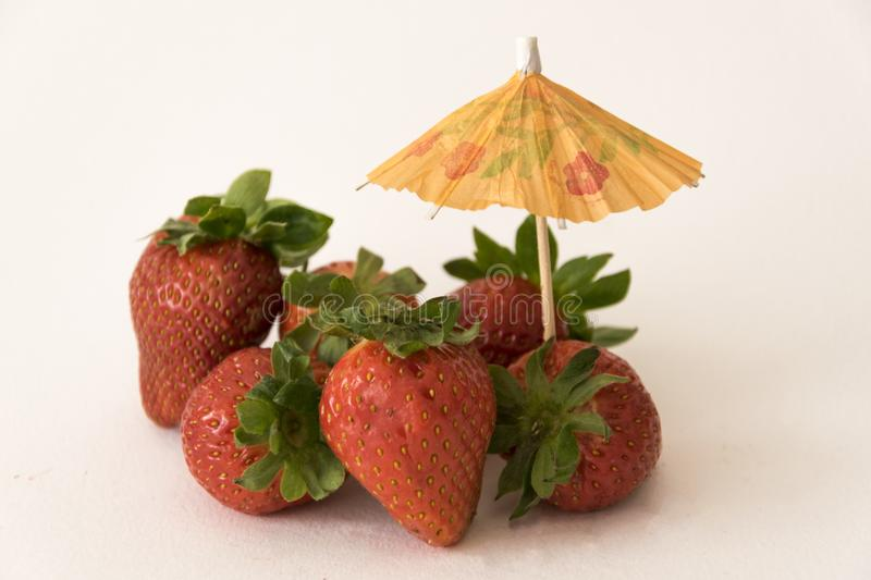 Strawberries with umbrella. Strawberries grouped with a decorative umbrella for refreshments stock photos