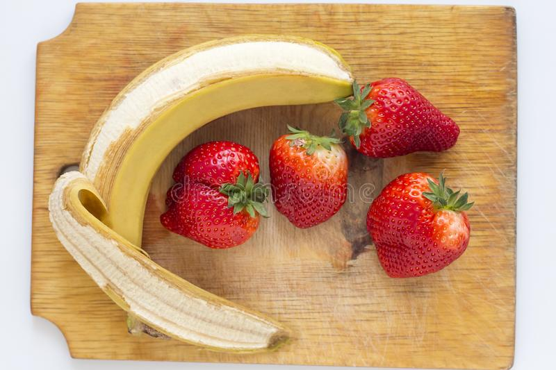 Strawberries and unpeeled bananas on a chopping Board.  stock photos