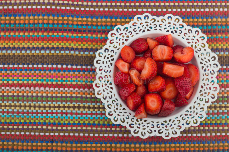 Strawberries on a white plate. Red Freshly cut strawberries on a white artistic plate stock photography