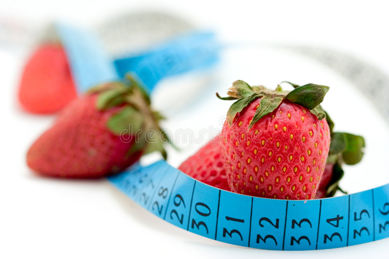 Strawberries wrapped around with a measure tape royalty free stock photo