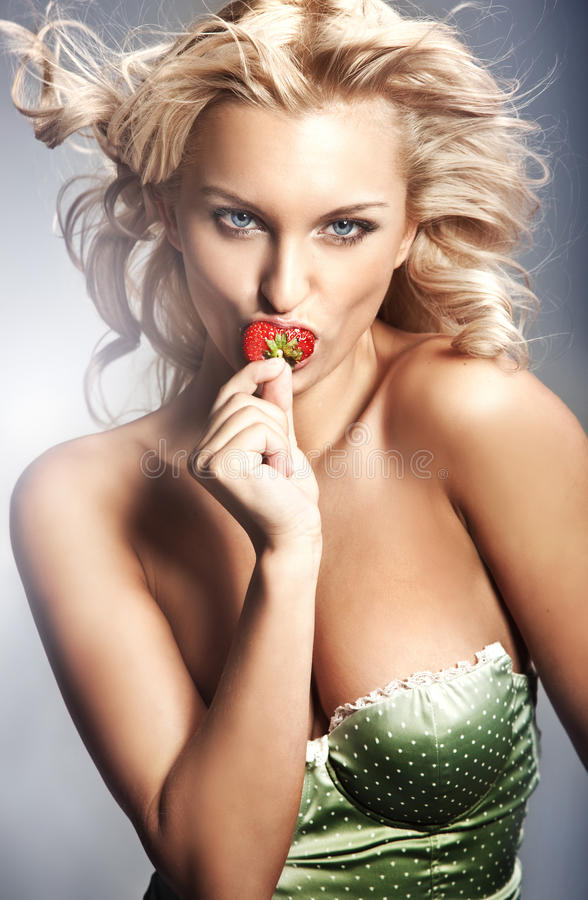 Strawberry. Young lady eating a strawberry royalty free stock photo